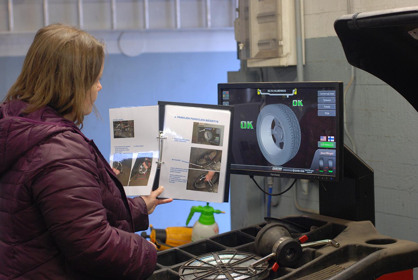 nainen katsoo graafista ohjetta opetuskorjaamolla
