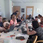 Kouluttaja ohjaa oppijoita, jotka istuvat pöydän ääressä tietokoneet edessään.