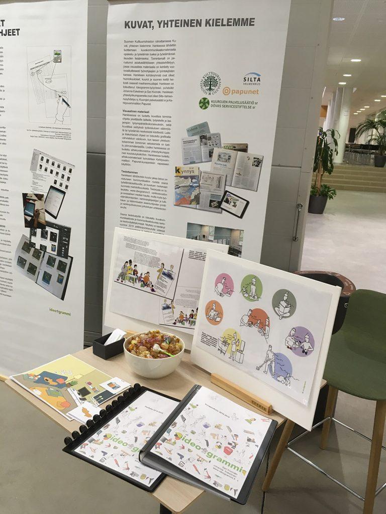 Näkymä Ideogrammin näyttelyyn, taustalla näyttelypostereita ja etualalla pöytä, jolla on Ideogrammin tekemää kuvamateriaalia.
