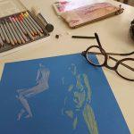 Työpöydällä on sininen paperi, jolle on valkoisella ja keltaisella kynällä hahmoteltu kaksi luonnosta alastonmalleista. Lisäksi pöydällä ovat silmälasit, penaali ja värikyniä kotelossaan..